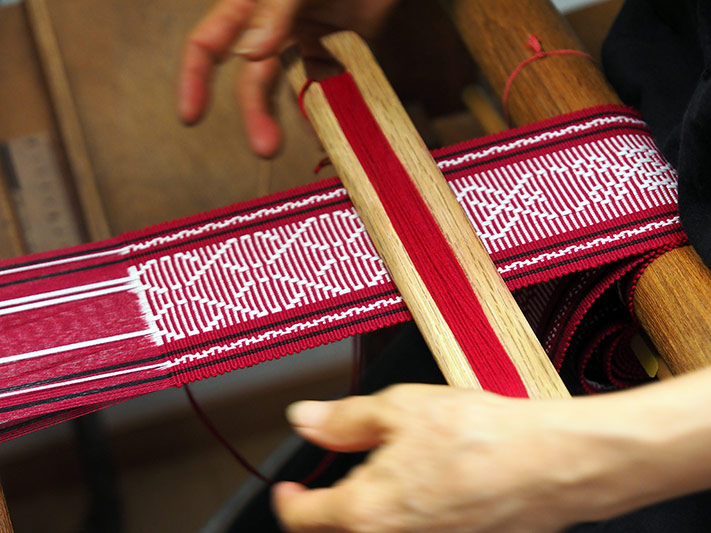Close-up of the weaver's hands as she makes the red and white obi sash.